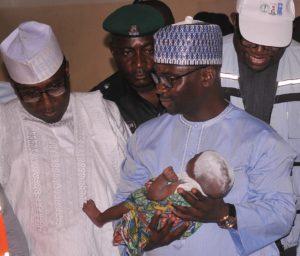 NEMA DG Sani-Sidi holds a newly born baby in IDP Camp