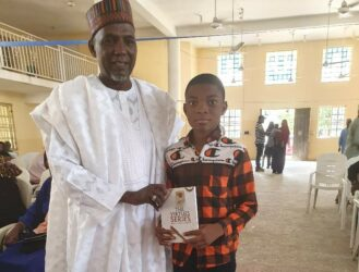 The Chairman of the Occassion, Surveyor Bashir Shettima present a copy of the book to a young boy who purchased a copy from his saving